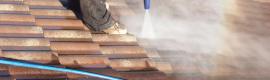 dakdekker bezig met het reiningen van een dak